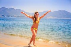 la muchacha delgada rubia en bikini salta en la playa Imagen de archivo