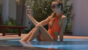 La muchacha delgada rubia se sienta en piscina baja hace Selfie