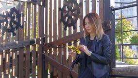 La muchacha delgada se coloca en parque y sostiene las hojas de otoño caidas y recoge el ramo almacen de video