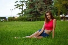 La muchacha delgada se sienta en hierba verde en un jardín enorme Foto de archivo