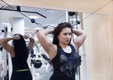 La muchacha deportiva hermosa construye los brazos y el pecho del músculo en el gimnasio Foto de archivo libre de regalías
