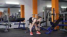 La muchacha deportiva hermosa joven realiza el deadlift rumano con un barbell en un gimnasio, fps de la opinión 60 de parte delan almacen de video