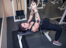 La muchacha deportiva hermosa que miente en el banco y las estructuras muscle los brazos Foto de archivo