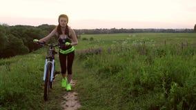 La muchacha deportiva rueda una bicicleta la muchacha aumenta una bicicleta en un altozano chica joven como ella camina una bici  almacen de video