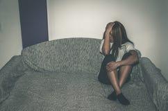 La muchacha deprimida y sola abusada como jóvenes que se sientan solamente en su sitio en la sensación de la cama desgraciada y l imagenes de archivo