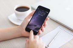 La muchacha desbloquea gris del espacio del iPhone 6 sobre la tabla Fotografía de archivo libre de regalías