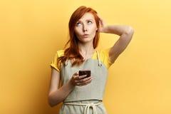 La muchacha desconcertada no conoce qué escribir a su amigo, fotografía de archivo libre de regalías