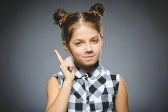 La muchacha descontentada y despectiva con amenaza al finger en fondo gris Imagenes de archivo