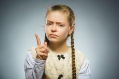 La muchacha descontentada y despectiva con amenaza al finger en fondo gris Fotografía de archivo