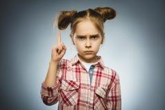 La muchacha descontentada y despectiva con amenaza al finger en fondo gris Imagen de archivo