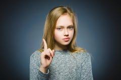 La muchacha descontentada y despectiva con amenaza al finger en fondo gris Foto de archivo