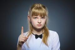 La muchacha descontentada y despectiva con amenaza al finger en fondo gris Imagen de archivo libre de regalías