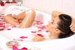 La muchacha descubierta atractiva disfruta de un baño con leche Fotos de archivo