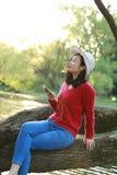 La muchacha descuidada china asiática está escuchando la música se sienta en un árbol por un río en parque del otoño de la primav Imagenes de archivo