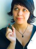 La muchacha desea algo escribir una etiqueta de plástico Imagen de archivo libre de regalías
