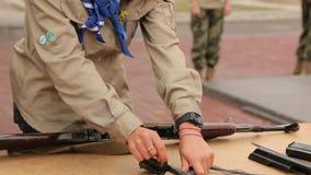 La muchacha desmonta el rifle de asalto almacen de video