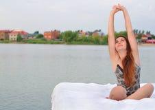La muchacha despertó en una cama en el agua Fotografía de archivo libre de regalías