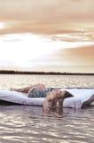 La muchacha despertó en una cama en el agua Foto de archivo libre de regalías
