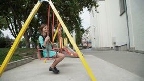 La muchacha despreocupada feliz con dos coletas en una cabeza seesaws en el parque almacen de video