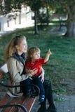 La muchacha detiene al niño pequeño que señala en algo Fotos de archivo libres de regalías