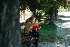 La muchacha detiene al niño pequeño que señala en algo Imagenes de archivo