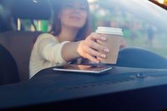 La muchacha detrás de la rueda de un coche Fotografía de archivo