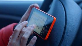 La muchacha detrás de la rueda de un coche que mira el mapa de la ciudad en un teléfono móvil 4K 30fps almacen de video