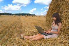 La muchacha detrás de una computadora portátil Fotografía de archivo libre de regalías