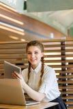 La muchacha detrás del ordenador portátil se está sentando en un caf Fotografía de archivo libre de regalías