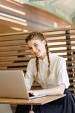 La muchacha detrás del ordenador portátil se está sentando en un caf Foto de archivo libre de regalías
