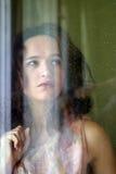 La muchacha detrás del vidrio Imagen de archivo