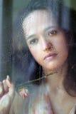 La muchacha detrás del vidrio Fotos de archivo