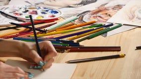 La muchacha dibuja bosquejo del lápiz en el papel Cierre para arriba almacen de video