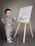 La muchacha dibuja con el cepillo en el caballete fotos de archivo