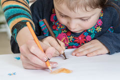La muchacha dibuja con la mamá Foto de archivo