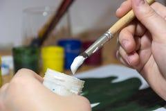 La muchacha dibuja el árbol verde, cucharadas, causando la pintura blanca en el th Imagen de archivo libre de regalías