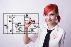 La muchacha dibuja el circuito electrónico del marcador Foto de archivo libre de regalías