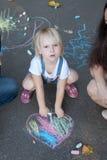 La muchacha dibuja en el asfalto Imagen de archivo libre de regalías