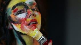 La muchacha dibuja en el cepillo en la pintura sí mismo almacen de metraje de vídeo