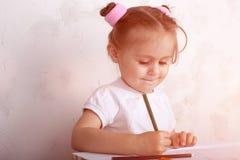 La muchacha dibuja en l?pices coloreados imagenes de archivo