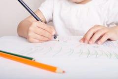 La muchacha dibuja en l?pices coloreados foto de archivo