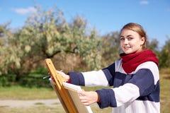 La muchacha dibuja en un caballete contra un fondo del cielo claro Foto de archivo
