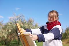 La muchacha dibuja en un caballete contra un fondo del cielo claro fotos de archivo