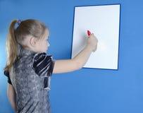 La muchacha dibuja en un tablero plástico blanco Imágenes de archivo libres de regalías