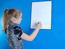 La muchacha dibuja en un tablero plástico blanco Foto de archivo