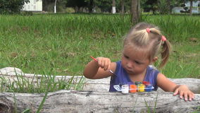 La muchacha dibuja la imagen con las pinturas en la madera almacen de video