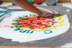 La muchacha dibuja las flores y el ` feliz en la arena, animación del día de fiesta del ` de la palabra de la arena, dibujando el Fotos de archivo libres de regalías