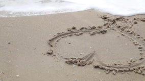 La muchacha dibuja un corazón en la arena cerca del mar almacen de video