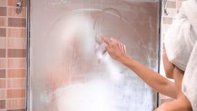 La muchacha dibuja un finger el coraz?n en el espejo del cuarto de ba?o almacen de metraje de vídeo