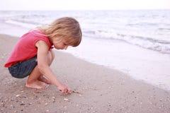 La muchacha dibuja un sol en la arena en la playa Imagen de archivo libre de regalías